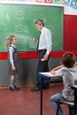Opinião lateral o professor and girl looking em cada um Imagens de Stock
