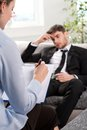 Oppressed man talking with psychologist men a problem on a reception for a Royalty Free Stock Images