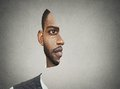 Optical illusion portrait front with cut out profile of a man surrealistic young isolated on grey wall background Royalty Free Stock Images