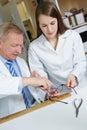 Optician helping trainee in workshop repairing glasses Royalty Free Stock Photo