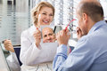 Optician offering glasses frames to client senior experienced female a elderly Royalty Free Stock Image