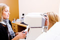 Optician testing eye pressure on client performing test Stock Image