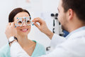 Optician with trial frame and patient at clinic Royalty Free Stock Photo