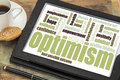 Optimism word cloud on digital tablet a with a cup of coffee and cookie Royalty Free Stock Photo