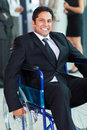 Optimistic handicapped businessman in a wheelchair Royalty Free Stock Photos