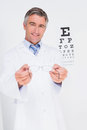 Optometrist holding eyeglasses out in medical office Royalty Free Stock Images