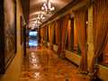 Opulent corridor with marble floor and curtains luxury paintings on the wall chandeliers ample light Stock Photo