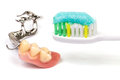 Oral hygiene toothbrush with toothpaste and partial dentures on white background Royalty Free Stock Images