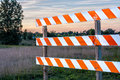 Orang and white road barrier orange striped barricade in rural setting Royalty Free Stock Photo