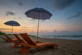 Orange beach chairs and parasols on sandy beach with morning sky