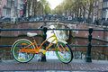 Orange  bicycle next to canal of Amsterdam Royalty Free Stock Photo