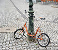 Orange bike chained to a pole Royalty Free Stock Photo