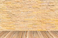 Orange brick wall as a nicely textured background on wood floor Royalty Free Stock Photo