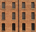 Orange Brick Wall with Twelve Windows and Gutter Royalty Free Stock Images