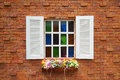 Orange brick wall and white wood window with colorful flowers Royalty Free Stock Photo