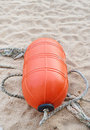 Orange buoy on the beach with rope Stock Photo