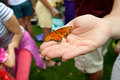 Orange butterfly rests on woman s hand at festival an Royalty Free Stock Images