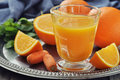 Orange and carrot juice in glass with mint fresh vegetables fruits on round tray Stock Photography