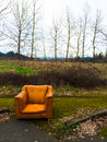 Orange chair urban decay and an abandoned next to some winter trees Stock Photo