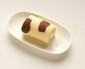 Orange chocolate roll cake in modern cream plate on cream background sweet Royalty Free Stock Photos