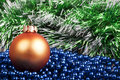 Orange christmas ball and blue beads on a background of green ga garland Stock Photography
