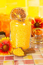 Orange citrus bath salts with natural healthy plant extracts displayed in a wooden scoop and clear glass jar on a tiled bathroom Stock Photo