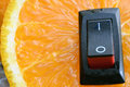 Orange close up with with inserted power switch. Royalty Free Stock Photo