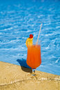 Orange cocktail stands on edge of pool. Stock Image