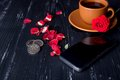Orange coffee cup with rose petals, mobile phone  and euro coins on the black background Royalty Free Stock Photo