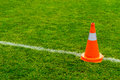 Orange cone on grass field Royalty Free Stock Photo