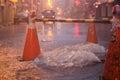 Orange cones around overflowing manhole Royalty Free Stock Photo