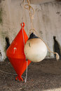 Orange conical buoy and white spherical buoy hanging outside wat Royalty Free Stock Photo