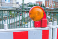 Orange construction warning street barrier light on barricade. Road construction on the streets of European cities Royalty Free Stock Photo