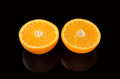 Orange cut into two pieces, on a black background. Royalty Free Stock Photo