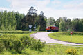 Orange Dump Truck moves on road on hill in green grass Royalty Free Stock Photo