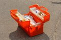 Orange emergency medical pack open in the asphalt road Royalty Free Stock Photo