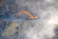 Orange excavator, digger in a granite quarry Royalty Free Stock Photo