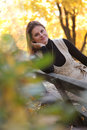 Orange fall young woman relaxing in autumn park Stock Photography
