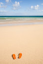 Orange flip flops at the beach summer travel background with a beautiful sandy white a blue sky and a pair of in sand Stock Photos