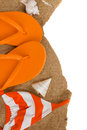 Orange flip flops and swimming suit on sand isolated white background Royalty Free Stock Photos