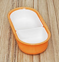 Orange folding plastic food box on the wooden background, kitche Royalty Free Stock Photo
