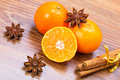 Orange fruit cinnamon sticks and anise stars on wooden table Stock Photo