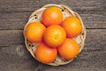 Orange fruit in wicker plate on vintage wooden table top view Stock Photos