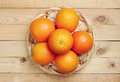 Orange fruit in wicker plate on wooden background top view Royalty Free Stock Photos