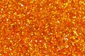 Orange glittering foil leaf shiny wrapping paper glitter texture background for Christmas holiday. Royalty Free Stock Photo