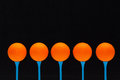 Orange golf balls on blue wooden tees Stock Images