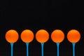 Orange golf balls on blue wooden tees Stock Images