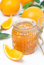 Orange jam in a glass jar and oranges vertical Stock Images