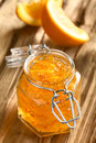 Orange jam in jar swing top on wood with slices the back photographed with natural light selective focus focus on the Stock Photography