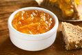 Orange jam in small bowl on wood with bread on the side photographed with natural light selective focus focus one third into the Stock Photos